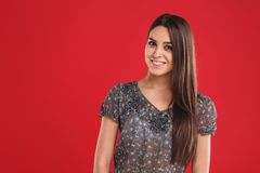 Portrait of young beautiful cute cheerful girl smiling looking at camera over red background. royalty free stock image