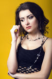 Portrait of a young beautiful dark haired concerned woman wearing black net top and glass beads looking worried and upset. Isolated on yellow background Royalty Free Stock Photos