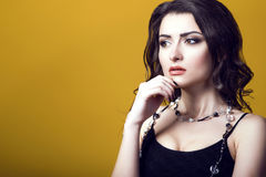 Portrait of a young beautiful dark haired concerned woman wearing black top and glass beads looking worried and thoughtful. Isolated on yellow background. Copy Royalty Free Stock Images
