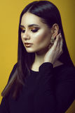 Portrait of young beautiful dark-haired girl with professional make-up in golden and copper colors hiding her hair behind the ear Royalty Free Stock Photo