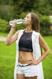 Portrait of young beautiful dark haired woman drinking water. At summer green park Royalty Free Stock Images
