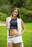 Portrait of young beautiful dark haired woman drinking water. At summer green park Stock Photos