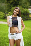 Portrait of young beautiful dark haired woman drinking water. At summer green park Stock Photography