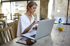 Portrait of a young beautiful elegant women relaxing after work on portable laptop computer during coffee break. Female freelancer sitting at the wooden table Royalty Free Stock Photos