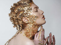Portrait of young beautiful fashion model with gold foil on face Royalty Free Stock Photography