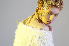 Portrait of young beautiful fashion woman with gold foil on face Royalty Free Stock Photo