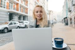 Portrait of young beautiful fashionable blond woman in warm clothes sitting in an outdoor cafe with laptop computer, drinking cup royalty free stock photos