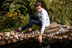 Portrait of young beautiful fashionable man against autumn garden. Royalty Free Stock Photography