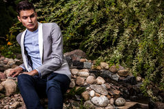 Portrait of young beautiful fashionable man against autumn garden. Stock Image
