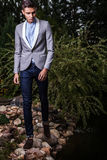 Portrait of young beautiful fashionable man against autumn garden. Stock Photo
