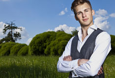 Portrait of young beautiful fashionable man against autumn garden. Royalty Free Stock Image