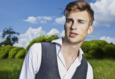 Portrait of young beautiful fashionable man against autumn garden. Royalty Free Stock Images
