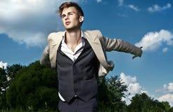 Portrait of young beautiful fashionable man against autumn garden. Stock Photos