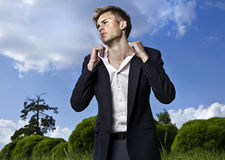 Portrait of young beautiful fashionable man against autumn garden. Royalty Free Stock Photos