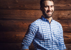 Portrait of young beautiful fashionable man against wooden wall. Royalty Free Stock Photo