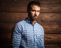 Portrait of young beautiful fashionable man against wooden wall. Stock Images