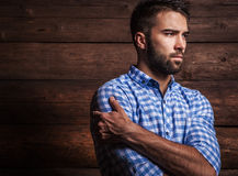 Portrait of young beautiful fashionable man against wooden wall. Stock Photo
