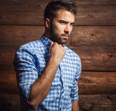 Portrait of young beautiful fashionable man against wooden wall. Photo royalty free stock image