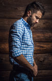 Portrait of young beautiful fashionable man against wooden wall. Stock Photos