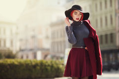 Portrait of young beautiful fashionable woman posing on the street. Model wearing stylish black wide-brimmed hat, red Royalty Free Stock Images