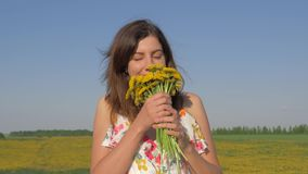 Portrait of woman in field with bouquet of yellow dandelion flowers sniffing him stock video footage