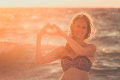 Young woman holding hands in heart shape. Sun and ocean in the b. Portrait of young beautiful female making heart shape with hands against sunset over sea Royalty Free Stock Photo