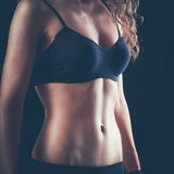 Portrait of young beautiful fitness woman, isolated on black background Royalty Free Stock Photos