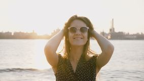 Portrait of young beautiful flirty European girl in sunglasses smiling at camera on New York city river sunset 4K. Portrait of young beautiful flirty European stock footage