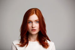 Portrait of young beautiful ginger girl over gray background. Royalty Free Stock Photo
