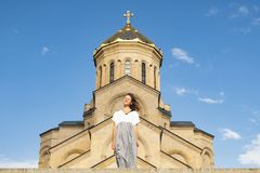 Portrait of a young beautiful girl against the background of Tsminda Sameba, an ancient Christian Church in Georgia. royalty free stock photos