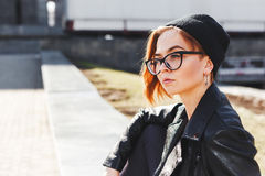 Portrait of a young beautiful girl in black big glasses and a knitted black hat Stock Image