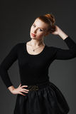 Portrait of a young beautiful girl in black clothing on a gray b Royalty Free Stock Photo