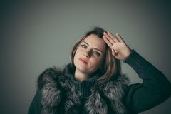 Portrait of a young beautiful girl in a black fur coat stock photography