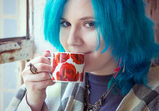 Portrait of a young beautiful girl with blue hair. Young beautiful girl with blue hair is drinking coffee; selective focus Royalty Free Stock Images