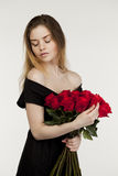 Portrait of a young beautiful girl with a bouquet of red roses Stock Images