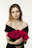 Portrait of a young beautiful girl with a bouquet of red roses Royalty Free Stock Photography