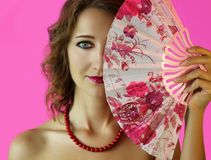 Portrait of a young beautiful girl with bright make-up and a fan in hands close-up on the pink background Stock Image
