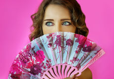 Portrait of a young beautiful girl with bright make-up and a fan in hands close-up on a pink background. Stock Images
