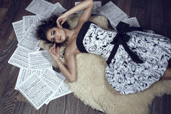 Portrait of young beautiful girl with curly hair  lying on the shipskin rug on the floor with sheets music thrown around her Royalty Free Stock Photography