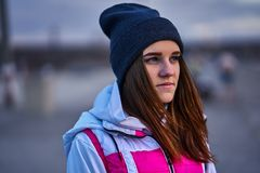Portrait of a young beautiful girl with dark brown hair in a sports hat and jacket in the first rays of the morning rising sun. In an autumn cold morning stock image