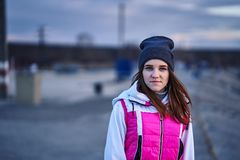 Portrait of a young beautiful girl with dark brown hair in a sports hat and jacket in the first rays of the morning rising sun. In an autumn cold morning royalty free stock images