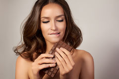 Portrait of a young beautiful girl with dark curly hair, bare shoulders and neck, holding a chocolate bar to enjoy the taste and royalty free stock images