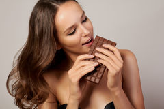 Portrait of a young beautiful girl with dark curly hair, bare shoulders and neck, holding a chocolate bar to enjoy the taste and a Royalty Free Stock Photography