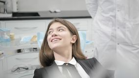 Portrait of a young beautiful girl in the dentist chair at dental clinic. Medicine, health, stomatology concept. dentist. Treating a patient. Woman smiling stock video