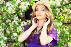 Portrait of young beautiful girl in dress and hat with long hair. Spring fashioned woman. Royalty Free Stock Image