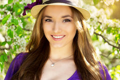Portrait of young beautiful girl in dress and hat with long hair. Spring fashioned woman. Stock Image