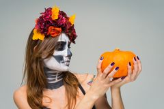 Portrait of young beautiful girl with fearful halloween skeleton makeup with a wreath Katrina Calavera made of flowers on her head. Holding orange pumpkin over royalty free stock photo