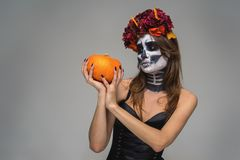 Portrait of young beautiful girl with fearful halloween skeleton makeup with a wreath Katrina Calavera made of flowers on her head. Holding pumpkin over gray stock image