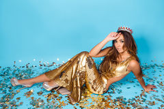Young woman posing in golden dress with crown. Portrait of young beautiful girl in golden dress and crown posing on blue background Stock Photos
