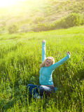 Portrait of young beautiful girl in a grassy field at sunset. Royalty Free Stock Images